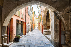 Old street in Villefranche-sur-Mer. Narrow cobblestone street with colorful buildings viewed though stone arch in medieval town Villefranche-sur-Mer on French Stock Image