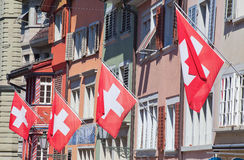 Old street in Zurich. Ancient street Augustinergasse in Zurich decorated with swiss flags Stock Photos