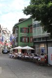 Old street in Zurich, decorated with swiss flags, Switzerland. Zurich, Switzerland - May 27, 2018 : Ancient street in Zurich, decorated with swiss flags. People Stock Photos
