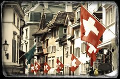 Old street in Zurich. Vintage photo of an old street in Zurich decorated with flags for the Swiss National Day, 1st of August Royalty Free Stock Photography