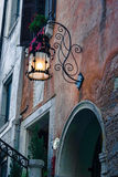 Old Streetlamp at Dusk in Venice, Italy. Close-up shot of an ornate old streetlamp against a brick building at dusk in Venice, Italy Royalty Free Stock Images