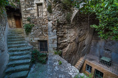 Old streets of Bonnieux. BONNIEUX, FRANCE - MAY, 2015: Stairs on the tiny old street and house in the rock with terrace, table and chairs at the balcony in the Stock Images