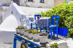 Traditional Greek street taverna with blue chairs . Naxos island, Cyclades. Old streets of Greece,view with tavernas and flowers,Naxos island stock image