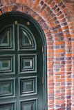 Green entrance arched door framed by brick arch of the building. Old strong painted arched wood entrance door with convex panels arranged in two rows framed by Royalty Free Stock Images