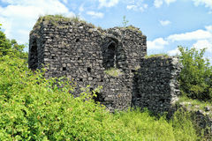 Old stronghold castle tower ruins in the green vegetation Stock Photo