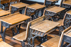 Old Student Classroom Desks. Close up of rows of antique student desks. Focus on desk in foreground stock photo