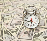 Old style alarm clock and on dollars background.  Stock Photography