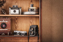 Old style, antique cameras on wooden shelf.  Photographer cupboard. Stock Image