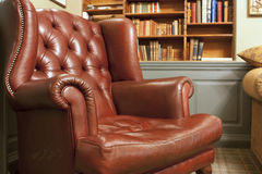 Old style armchair in front of bookshelves. Old style chesterfield style brown leather armchair in front of bookshelves Royalty Free Stock Photos