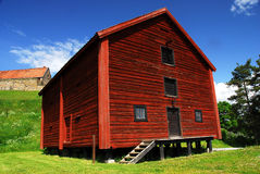 Old style barn. An image of an old style red painted barn, not in use but preserved for tourist attraction. Background shows fortress, blue clouds, green grass Royalty Free Stock Photo