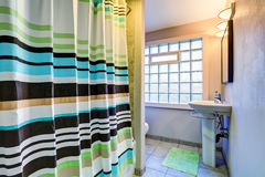 Old style Bathroom interior with colorful stripped curtain Stock Photo