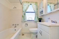Old style bathroom interior with white cabinets. Bath tub, toilet and nice green curtain on the window. Northwest, USA royalty free stock photo