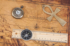 Old style brass pocket watch and cross on  map. Old style brass pocket watch and cross on antique map Royalty Free Stock Images