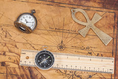 Old style brass pocket watch and cross on map Stock Photography