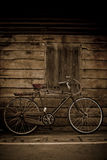 Old style brown bicycle and wood door Royalty Free Stock Photo