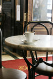 Old Style Cafe. Empty cup of coffee over a table in an old style coffee house Royalty Free Stock Photo