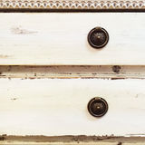 Old style chest of drawers. Old style white chest of drawers with metal handles Royalty Free Stock Image