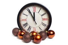 Old style classic clock with roman numbers showing almost twelve o` clock and some colorful christmas balls isolated on white bac. Kground, front view stock image