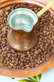 Old style copper coffee pot cezve and beans. On the plate Royalty Free Stock Photo