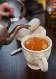 Old-style copper kettle pouring tea to white cup Stock Image
