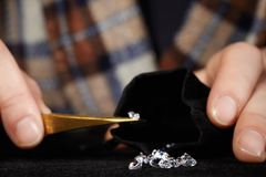 Smuggler of diamonds preparing gems for dealing with velvet bag. Old style diamond smuggler watching quality of his goods Royalty Free Stock Images