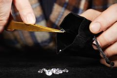 Smuggler of diamonds packing gems to velvet bag for dealing. Old style diamond smuggler watching quality of his goods Stock Images