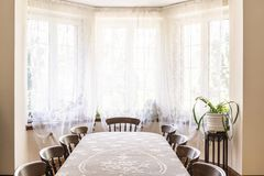 Old style dining room interior with a big window decorated with royalty free stock images