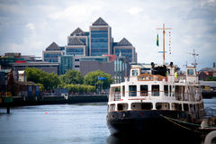 Old Style Ferry boat. Docked in Dublin, Ireland with modern business headquarter buildings in the background Royalty Free Stock Photos