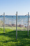 Old style fishing net hanging to dry near seashore Stock Photos