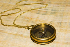 Old style gold compass. On papyrus background royalty free stock images