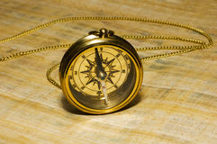Old style gold compass. On papyrus background royalty free stock photo