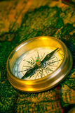 Old style gold compass. On antique world map Royalty Free Stock Photos