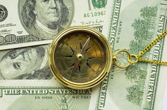 Old style gold compass with chain. On dollar background stock photos