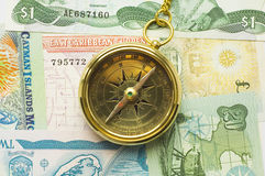 Old style gold compass with chain. On money background stock photos