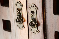 Old style handle of an antique wooden cupboard. Copper art-deco handles on doors of an old furniture Stock Image