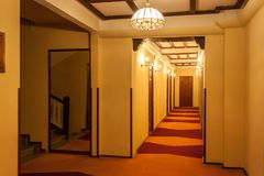 Old style hotel hallway with wooden brown doors, reddish carpet, and yellow walls. Mirror seen near the floor stairs.  stock images