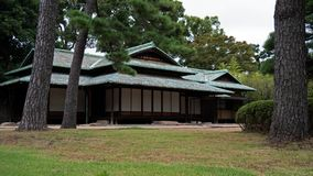 An old style Japanese house sits in a classic Japanese style garden. royalty free stock photography