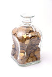 A old style jar filled up with coins. A old style jar filled up with copper coins photographed on a white background Royalty Free Stock Image
