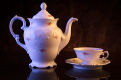 Old-style kettle with cup of tea on black Royalty Free Stock Images