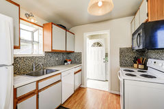Old style kitchen interior with hardwood floor and white appliances. Backsplash. View of opened entrance door. Northwest, USA Royalty Free Stock Photography