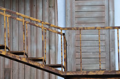 Old style ladder and wooden door. Old or abandon ladder made in iron, full of rust, and old wooden door. Composed as harmonious color and shape Stock Photos