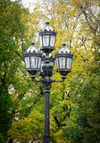 Old-style lamp post at the park in autumn Royalty Free Stock Images