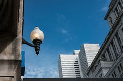 Old-style lamp seen by a distant office block. The old-style lamp appears to be on in daylight, attached to an old style building. The distant shows a modern Stock Photo