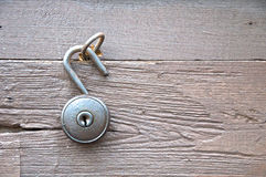Old style latchkey unlock. From metal hook on wood background Stock Photos