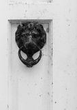 Old style lion's head knocker on white door Royalty Free Stock Image