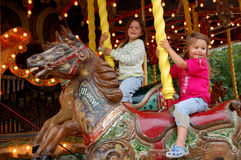 Old style merry-go-round. Two young girls on an old style merry-go-round depicting horses. Les Tuileries garden, Paris, France Royalty Free Stock Photos