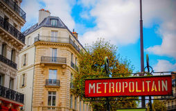 Old style Metro Sign in Paris with Architecture in background, France. During daytime Royalty Free Stock Photos