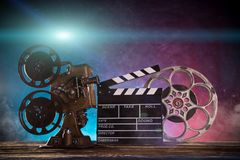 Old style movie projector with clapperboard, close-up. Old style movie projector with clapperboard and vintage steel reel, close-up Stock Image