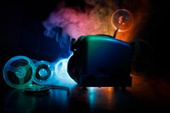 Old style movie projector, close-up. Film projector on a wooden background with dramatic lighting and selective focus. Movies and. Old style movie projector Royalty Free Stock Photo