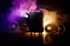 Old style movie projector, close-up. Film projector on a wooden background with dramatic lighting and selective focus. Movies and. Old style movie projector Royalty Free Stock Photography